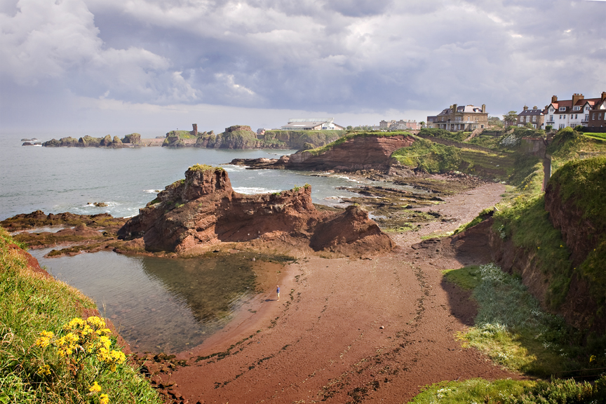 Red sandy rock coastline with green grass, Dunbar