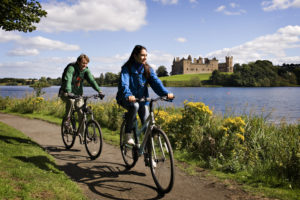 Cycling on footpath past loch and Linlithgow Palace